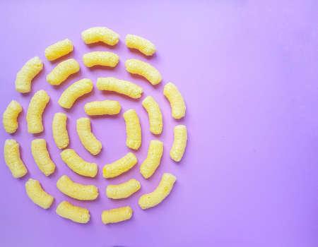 Yellow corn sticks on a purple background. High quality photo