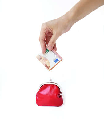 A womans hand puts money in a red purse with a metal lock on a white background. Saving money. High quality photo. Place for text.