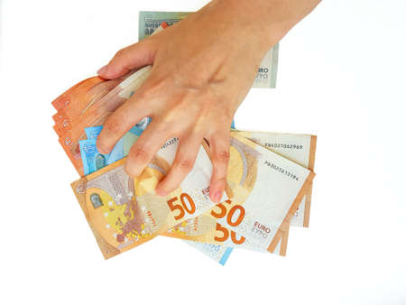 The womans hand holds the paper money of the euro against a white background. Greed. Debts. Salary. Credit. High quality photo Archivio Fotografico - 151073354