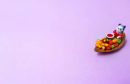 A traditional ceramic Thailand souvenir boat with fruit and a woman on a bright purple background. . High quality photo