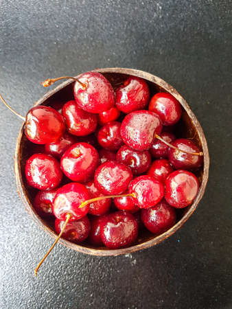 Red juicy ripe cherry in a wooden plate on a black background. High quality photo Banque d'images
