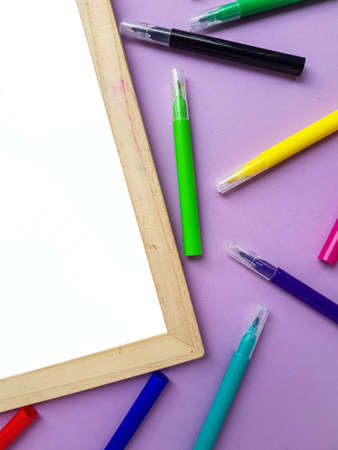 Empty clean white sheet for the buyers text on the purple background and school supplies, pencils. Back to school. High quality photo