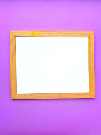 White empty clean school board on a purple background with a wooden brown frame. Back to school. Mochup. High quality photo