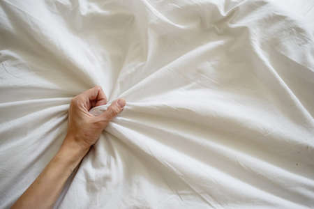 Close up sexy woman hand pulling and squeezing white sheets in ecstasy in bed. Orgasm on white bed. Sex and erotic concept. High quality photo Фото со стока