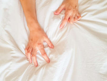 Close up sexy woman hand pulling and squeezing white sheets in ecstasy in bed. Orgasm on white bed. Sex and erotic concept. High quality photo Archivio Fotografico
