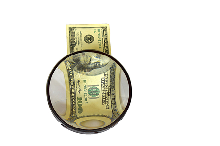 Dollar bill under a magnifying glass, isolate. Concept: check the money without leaving the cashier.