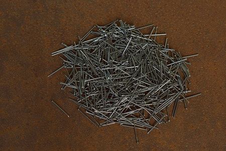 A pile of nails against the background of a sheet of rusty iron.