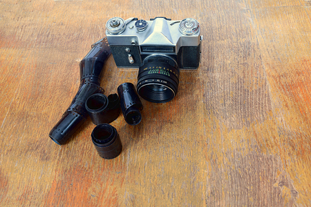 Old camera, films and cartridge on a wooden table. Stock fotó