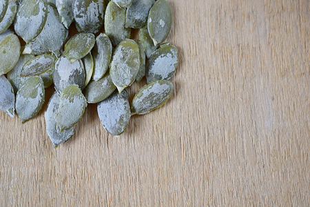 Peeled pumpkin seeds in an orderly manner on a wooden background.