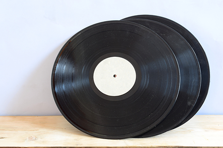 Old vinyl records on a wooden table in wind position.
