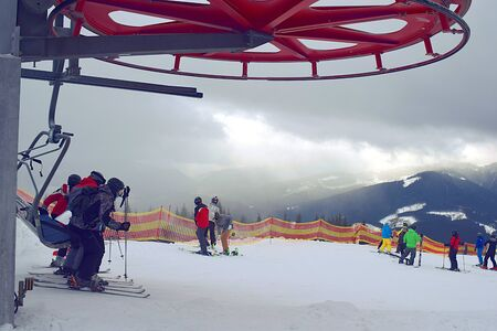 Skiers descend from the ski lift at the top of the mountain. Stock fotó