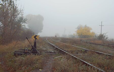 Railway arrow in the thick fog in the autumn, the concept of decision making in conditions of uncertainty.