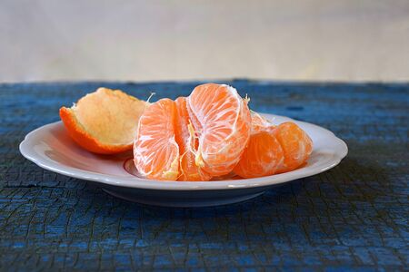 Peeled mandarin on a plate on a blue table, macro. Stock Photo