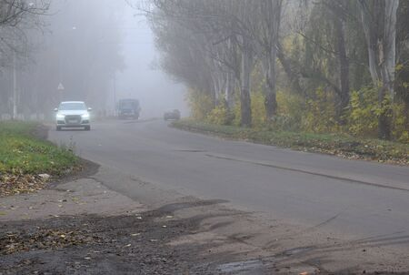 The car is moving along the road in a fog. Autumn landscape.