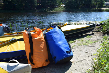 Kayaks and airtight gear bags on the beach while parking.
