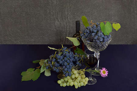 Two grape varieties in vases and a bottle of wine.