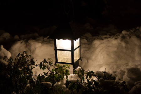 street lamp in the snow near the hedge Stock Photo