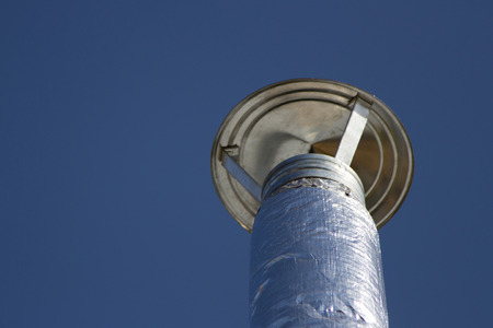 flue: Flue pipe wrapped with foil against the blue sky