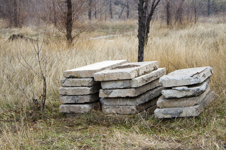 concrete blocks: old abandoned concrete blocks stacked in the grass Stock Photo