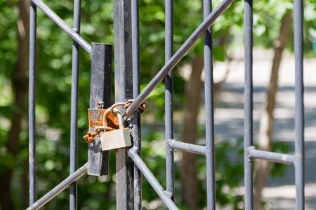 rejas de hierro: candado oxidado en la puerta de barrotes de hierro