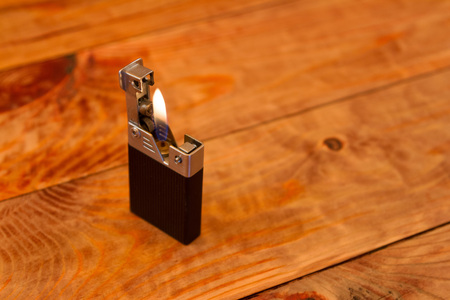 A working gas lighter on the wooden table