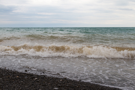 black pebbles: colored water in the wake of the Alakol lake and a beach with black pebbles Stock Photo