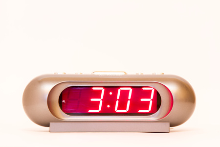 oclock: electronic clock alarm clock with red illumination and the time 3:03