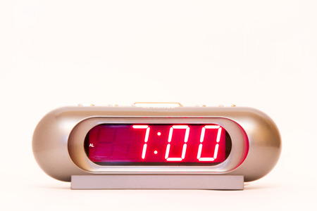 electronic clock alarm clock with red illumination and the time 7:00
