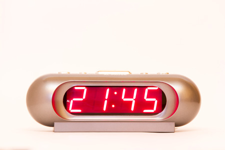 electronic clock alarm clock with red illumination and the time 21:45 Stock Photo