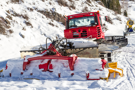 snow grooming machine: broken snowcat on the edge of the slopes and snow gun