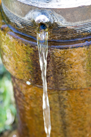 A stream of water from a hole in an old and rusty pipe