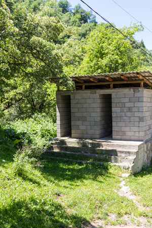 Public toilet made of bricks located in the mountains along the road