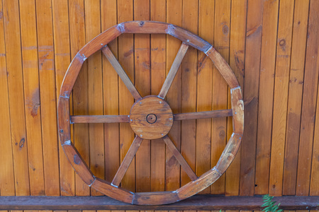 Old wooden wheel after restoration near the wooden wall