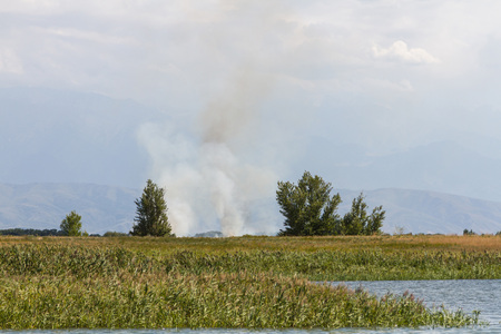 crater lake: smoke by the lake from a burning field Stock Photo