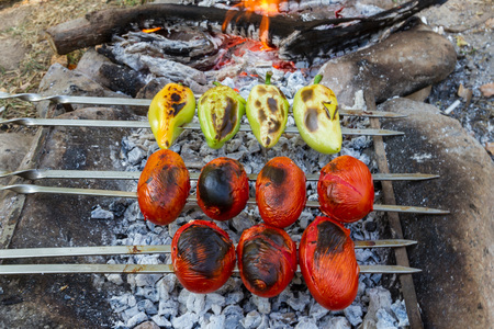 Pepper and tomatoes are cooked on charcoal