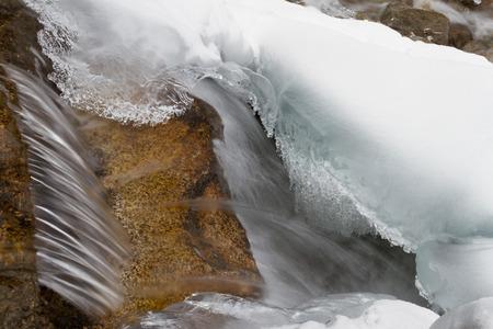 water splashes freeze in a small beautiful waterfall Фото со стока