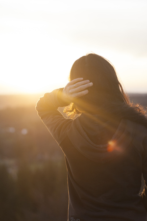 Beautiful black haired young girl watching sunset at rural environment, in the mountains. Touching her hair