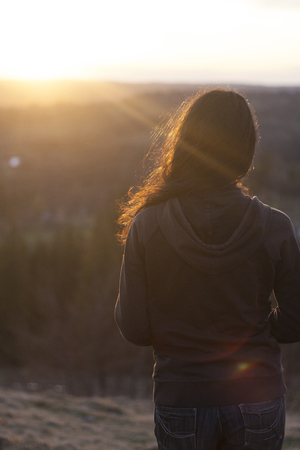 Beautiful black haired young girl watching sunset at rural environment, in the mountains. Reklamní fotografie