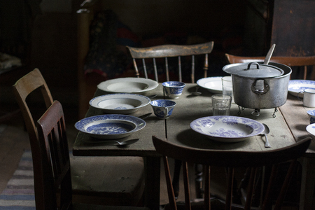 Vintage set table with old plates and wooden chairs in a poor interior Reklamní fotografie