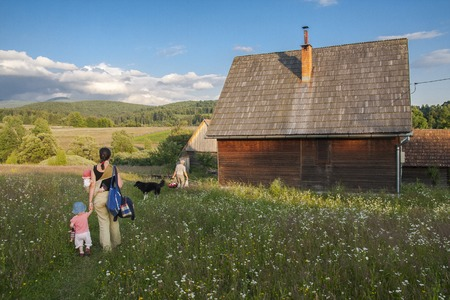 Rural family arriving home to wooden house