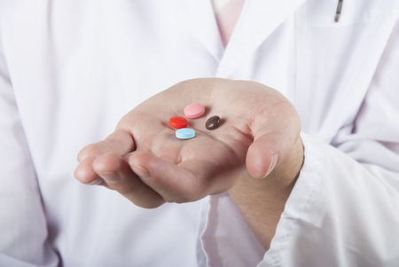 antibiotic pink pill: Closeup of a hand holding some colored pills