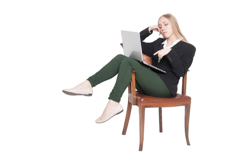 elbow chair: Dreamy young lady in black jacket and green jeans sitting comfortably in an elbow chair, searching for information in her laptop, legs over the elbow, with copyspace (isolated on white background)