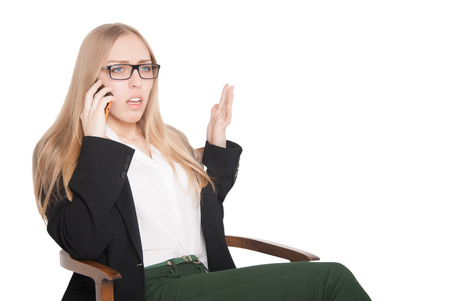 gesticulating: Beautiful young business woman in glasses sitting in a chair, talking on cell phone and gesticulating emotionally (isolated on white background)