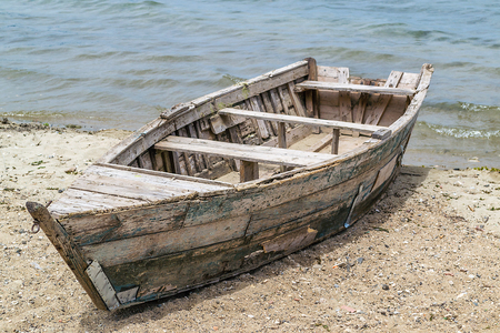 Old wooden boat, forgoten on the lake beach