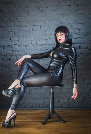 beautiful slim woman in leather suit sitting on a chair cross-legged