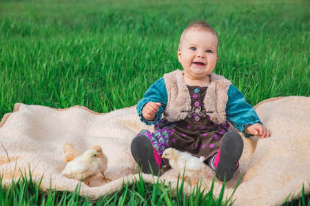 baby in a colorful dress on the lawn with chickens
