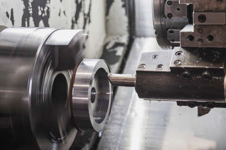 A milling cutter in a CNC machine cuts a metal workpiece that rotates at high speed Stockfoto