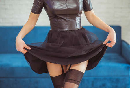 Attractive woman lifted her dress and shows stockings