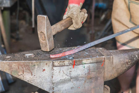 The blacksmith hits the red-hot rod with a hammer and pieces fly off the workpiece