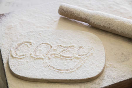 """The word """"Cozy"""" written in flour on the kitchen table"""